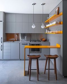 The kitchen and eating area inside a compact 330 square feet apartment in Venice, Los Angeles. Full height hidden storage delineates the space and provides visual and acoustic privacy. Minimal material palette minimizes distraction and maximizes the spatial quality of the area. The uninterrupted layer of warm grey enhances this effect and gives the yellow dining surface and shelves the opportunity to shine with its vivid hue. This is the work of Vertebrae Architecture + Design. Image via…