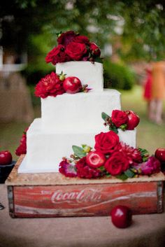A retro, vintage wooden Coca-Cola crate looks great as a stand for this pretty red and white wedding cake.