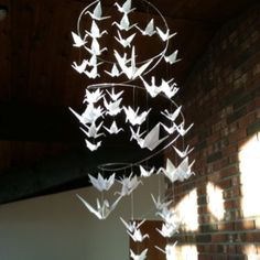Origami paper crane mobile that looks like a spiraling chandelier.  Great as wedding decorations.