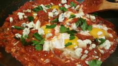 COZY NIGHT SHAKSHUKA  INGREDIENTS Olive Oil 1 cup large yellow onion, chopped 1 red and 1 green peppers, chopped 2 garlic cloves, peeled, chopped 1 tsp lime juice 1 tsp ground coriander 4 tblsp sweet paprika 1 tsp ground cumin 1 tsp chili powder Pinch red pepper flakes (optional) Salt and pepper 2 cans (14oz) diced tomatoes ½ can tomato paste 1/2 tsp sugar 6 large eggs ¼ cup chopped fresh parsley leaves 1/2 cup crumbled bleu cheese 1/4 cup sliced Olives 2 tblsp capers INSTRUCTIONS Heat 3…