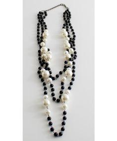 Maxi collana a tre giri di perle sintetiche con allacciatura tramite gancetto in metallo.