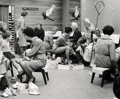 Nederlands: Sinterklaas te midden van andere klanten en verkoopsters bezig met het passen van schoenen in een Bata schoenenwinkel in Haarlem. Nederland, Haarlem, 8 november 1960.  English: St. Nicholas in a Bata shoe shop. The Netherlands, Haarlem, 1960.