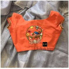 Stunning silver color jute saree and orange color designer blouse. Blouse with floral and bird design pretty hand embroidery thread work. 04 June 2018