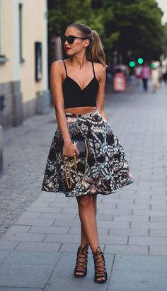 Kenza Zouiten is wearing a black crop top from Chicy, printed skirt from H&M, bag from Yves Saint Laurent, sunglasses from Prada and the lace up shoes are from Zara