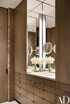 The master bath's travertine counter-top is framed by cerused-oak paneling   archdigest.com