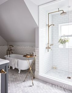 Designer Allison Wilson's third-floor bathroom has a charming look thanks to a restored vintage bathtub and traditional antiqued-brass fixtures. | Photographer: Angus Fergusson