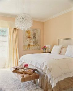 Pale Peach Walls And Drapes Instantly Soften A Bedroom,while A Glass  Chandelier And Lucite Bench Legs Help To Relfect Light.