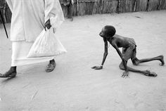"""A well nourished Sudanese man steals maize from a starving child during a food distribution at Medecins Sans Frontieres feeding centre at Ajiep, southern Sudan, in 1998"""