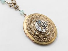 Steampunk Locket Necklace  Featuring a silver watch movement gears gold floral filigree & blue Swarovski crystal