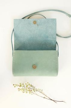 This small, sweet purse is made of gorgeous, vegetable tanned Italian leather in a beautiful pastel hue. Somewhere between sage and mint, the bluish green tint of the leather is absolutely perfect for spring and summer. A natural veg tanned, adjustable cross-body leather strap completes