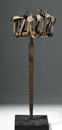 West Africa, Nigeria, Yoruba Tribe, 19th century CE or earlier. Rare Opa Osanyin herbalist's staff. Made of hand-forged iron with staff in a long spear shaped support to which a ring of applied birds have been added, large bird would have once been at top with figure below with offering vessel in its hands. The Yoruba believe that a large bird surrounded by smaller birds symbolizes the power of good over evil and the ability to control spirits and supernatural forces. As such opa osanyin...