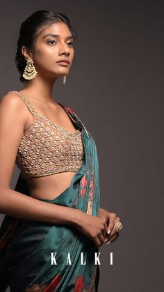 Emerald green ready pleated saree in satin with floral print and ruffle layer on the hem. Matched with a contrasting latte beige blouse in raw silk heavily embroidered with zardozi, pearls, cut dana and thread work in floral buttis. Designed sleeveless with sweetheart neckline. Waist highlighted with a matching embellished belt.