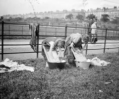 Girls washing laundry in metal basins on Glasgow Green, early 20th century.