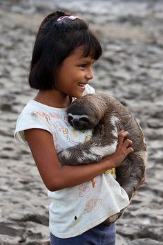Peru...A girl and her sloth from the rainforest, Peru