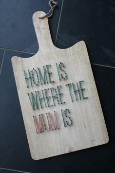 String-art pattern text HOME IS WHERE THE MUM IS - MINI on a cutting board.