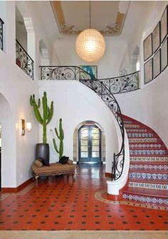 Kate Walsh's 1920s Spanish Home in LA via HookedOnHouses - love the tile on the stairway & the handrail - hate the disco ball fixture