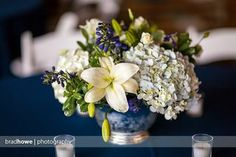 White and blue centerpiece with hydrangea, lilies, delph, roses, and lisianthus