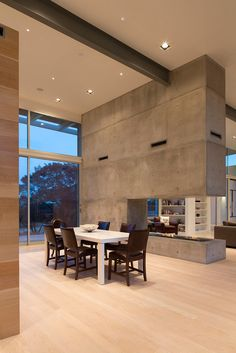 The dining room in this modern house features a tall ceiling and huge windows that work together to create an airy feel in the space while the concrete fireplace prevents the openness from feeling empty. Large steel I-beams that run through the house as well as the concrete add an industrial touch to the interior.