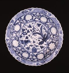 Large porcelain serving dish with bracket-lobed edge painted in underglaze blue and reserved decoration; inside with a raised white relief design of lotus blooms seen from different angles, against a blue ground; the centre with various plants, including melon, grape vines, morning glory, water weeds and plantain; the rim with a wave design; the outside with a band of lotus scrolls contained within a border of lines; the base unglazed.
