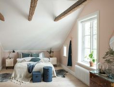 Attic bedroom with exposed beams and pastel pink walls