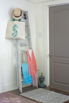 An old ladder is given new life as a coat rack by the front door #home #decor