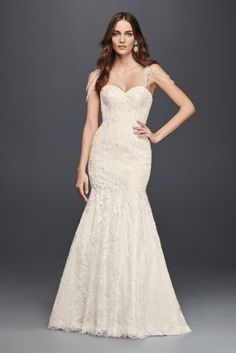 The beaded swag straps on this tulle and lace mermaid wedding dress are a sophisticated nod to the 1920s while the contouring silhouette is totally of-the-moment. A scalloped lace border trims the romantically flared skirt.   Galina Signature, exclusively at David's Bridal  Polyester  Chapel train  Back zipper; fully lined  Dry clean  Imported  Also available in extra length