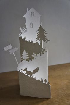 handmade Christmas card by mahaut Lemoine ... She says this is a cutting project for school.  ... all white ... cascade card fold with a delightful cut border along the top ... looks like a country road leading to a house ... probably could make a cut file for somethig like this .... d