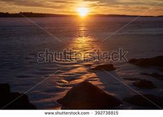 Stock Photo: Sunset at a frozen lake in the winter evening in Finland. Warm colors of the setting sun on cold ice.