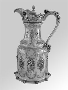 "An American Coin Silver covered pitcher, mark of William Forbes for Ball, Black & CO., New York, circa 1845: Of paneled form with a leaf-capped handle, chased and engraved with acanthus leaves enclosing floral and foliate cortouches, the helmet form upper rim repeating the chasing, the incurved cover with a beaded border, one panel engraved as a presentation ""F & MTC / TO / W. PITBLADDO""; height is 12 1/2 inches, weight is 39.15 Troy ounces."
