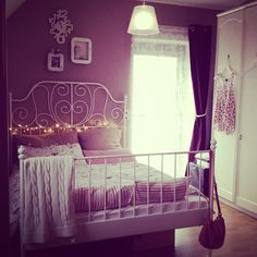 Dark pink walls with cast iron ikea bed.