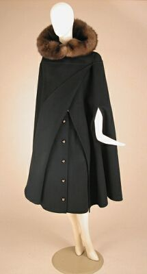 Valentino Couture Black Skirt and Cape Ensemble   Italian, 1964   Of double-faced cashmere, knee length, the A-line skirt closing at front with buttons inset with gilt-metal, slanted welt pockets, the cape with arm slits and optional hood trimmed in sable