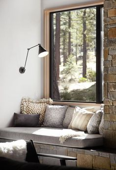 We love the built-in lighting, pillows, and stone in this window-seat reading nook.