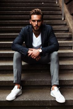 A charcoal wool blazer and grey suit pants will showcase your sartorial self. Dress down this getup with white low top sneakers. Shop this look on Lookastic: https://lookastic.com/men/looks/charcoal-blazer-white-v-neck-t-shirt-grey-dress-pants/17850 — Charcoal Wool Blazer — White V-neck T-shirt — Grey Dress Pants — White Low Top Sneakers