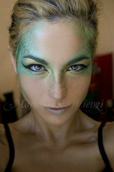 Siren/Mermaid greens and blue scales fanning out from eyes.