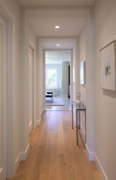Modern hallway lighting and decor. recessed LED lighting in hallway area to illuminate a dark narrow space. White hallway with hardwood floors and recessed lighting. Flur Design, Plafond Design, Hall Design, Lobby Design, White Baseboards, Modern Baseboards, Baseboard Styles, Baseboard Trim, Baseboard Ideas