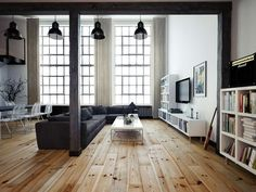 A space for living and entertaining. A raw wooden floor is the main point of the room. The space is simple and honest, with a white set of shelves and a grey sofa. The accent is made of the industrial lamps and the wooden beam and pillar