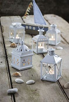 Assorted lanterns painted white great for a beach wedding.