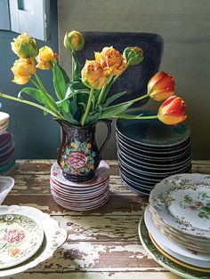 Yellow tulips in a vintage jug bearing a floral motif and stacks of Nikki Tibbles's vintage dinnerware on a rustic wooden tabletop with distressed white paint Tulip Dining Table, Spring Flower Arrangements, English Country Decor, Ranch Decor, Country House Interior, Bohemian Bedroom Decor, Vintage Dinnerware, Yellow Tulips, Western Decor