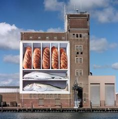 Art by Johnny Beerens on a grain silo at Breskens, The Netherlands:  Five loaves and two fishes to remind viewers of the Bible story.  Beerens painted an image of himself into the eye of the fish on the bottom.   (1997)