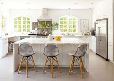 A custom kitchen island finished in Calcutta gold marble is flanked by a trio of wire Modernica chairs.