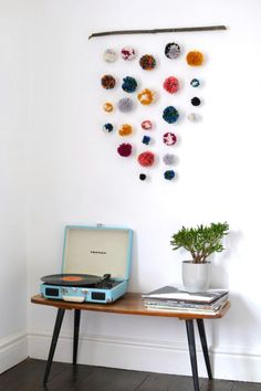 Pom Pom Wall Hanging By BurkatronPunchy pom poms — threaded and anchored to a branch or stick — make a cheerful antidote to a bare, white wall. #refinery29 http://www.refinery29.com/summer-diy-projects#slide-21