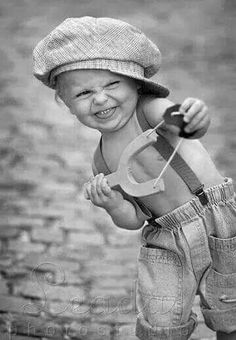 Black & White photo of an adorable little guy in old-fashioned clothes and a sling-shot.