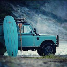 Blue Land Rover Defender at the beach.
