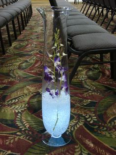 Ceremony aisle markers using 3 ft clear pedestal vases filled with clear crystal ice, dendrobium orchids, and under water lighting.