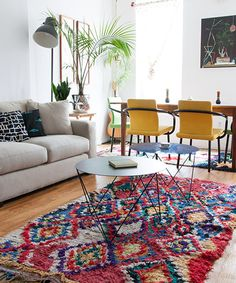 Cheery yellow chairs and a colorful vintage rug add oomph to an apartment.