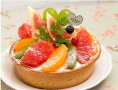 Seasonal Fruits Tart季節のたっぷりフルーツタルト Luxurious tart with plenty of seasonal fruits + whipped cream + custard cream + fruits and strawberries topping. 季節のフルーツをふんだんに使用した贅沢なタルト。カスタードクリームのタルトにホイップクリームを重ね、旬のいちごやたっぷりのフルーツを彩り鮮やかに飾りました。