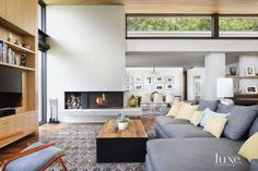 A wool Kalaty carpet from Oriental Rug Gallery of Texas establishes the color palette in the open living room, which is furnished with a sectional from Crate and Barrel and a coffee table from Room & Board that features a hickory top and steel sides. Enabler installed the wood ceiling.
