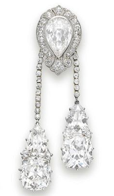 A Belle Époque Diamond Lavaliére Pendant   designed as an old mine-cut diamond scrolled pierced plaque, centering upon a bezel-set pear-shaped diamond, suspending two collet-set diamond tassels each terminating with a pear and cushion-cut diamond, mounted in platinum-topped gold (circa 1900).
