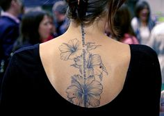 Beautiful hibiscus flowers and hebrew inscription tattoo on back