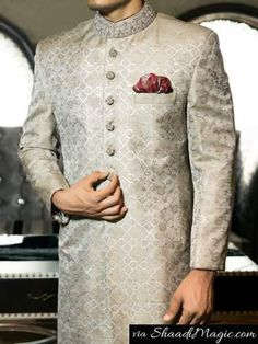 Junaid-jamshed-silver shade  Another Jamawar fabric cloth that has been designed with block print all over the Sherwani. The Sherwani has consisted of hand embroidery on the collar, sleeves and on the buttons with a maroon puffed handkerchief.